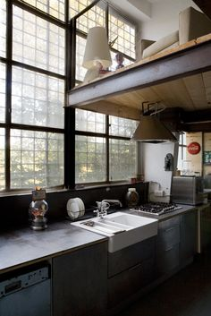 Factory loft kitchen with gorgeous windows and a mezzanine over hanging the kitchen......utilizing space to the max.....cleverly conceived..