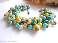 *Ocean spray*  Hand crafted charm bracelet, made with glass pearl beads, in blue, yellow, teal and peach, all assembled on a antique gold plated curb chain with added extender and lobster clasp!