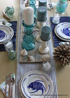 Coastal Tablescape: Blogger found rough boards while junking then dry brushed with grey paint. metal fish plates mixed with white stoneware.
