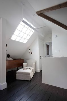 格子の入った大きな天窓のある勾配天井の下のリーディングヌック 一人掛けのソファ