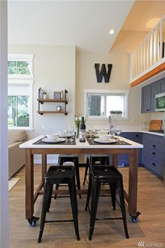The cozy, cabin-like exterior of this 399-square-foot Washington tiny home gives way to a modern, wood-finished interior that includes a full kitchen and bathroom, a living room, bedroom and loft. The cottage is family-friendly and downright stunning — and it's been repinned more than 40,000 times on Pinterest. Just take a look at this kitchen! Click through for more small space design inspiration from this tiny house in Washington.