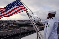 Aviation Boatswain's Mate (Handling) Airman Jackie L. Chess, right, salutes as Aviation Boatswain's Mate (Handling) Airman Jose A. Dominguez Rodriquez raises the American flag.