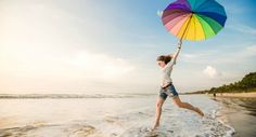 Cheerful caucasian young woman with rainbow umbrella having fun on the Jimbaran beach on Bali before sunset with beautiful ocean and blue sky on background.
