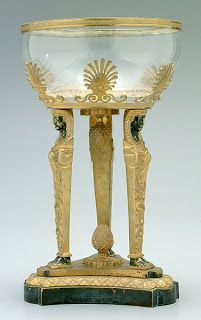 Cut glass bowl on base with three ebonized Egyptian female standards, anthemion border, descending bellflower and petal decoration throughout, drop and base mounted blossom finial, cut glass bowl with ormolu mounted rim, probably French, 19th century