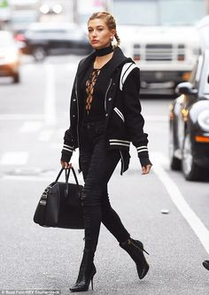So chic: Hailey layered on a black and white varsity style jacket and carried a Givenchy h...