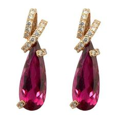 Pear Shaped Rubellite Earrings Wixon Custom  These wonderful gemstone earrings were designed and created in-house by Wixon Jewelers' designers. They feature 4.62-carats of pear shaped Rubellite gemstones from Brazil. The stones are set in a combination of 18k white and rose gold with a modern styled ribbon wrap design. Too add even more beauty to these earrings, the goldsmiths added almost a half-carat of round diamonds into these earrings!