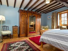The Master bedroom at Yanwath Gate Farm in Ullswater has a king sized bed, stunning views and original oak ceiling beams with antique furniture.