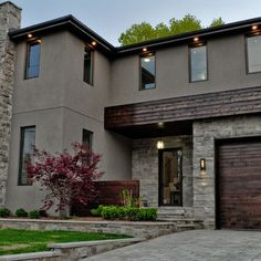 A modern home design with a flush wooden garage door is a stunning design. Notice the use of traditional building materials such as wood and stone; yet the overall effect is a contemporary style. Stucco And Stone Exterior, Stucco Homes, Modern Exterior, Exterior Design, Exterior Signage, Exterior Color Schemes, Exterior Paint Colors For House, Paint Colors For Home, Colour Schemes