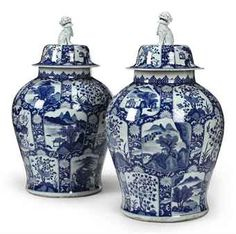 A MASSIVE PAIR OF BLUE AND WHITE JARS AND COVERS   19TH CENTURY   In Kangxi style, the swelling sides tapering to a flat base, decorated with an overall pattern of shaped panels showing landscapes or flowering plants reserved on a blue ground of scrolling chrysanthemum vine, a classic border on the short necks and the domed covers surmounted by Buddhist lion knops  33¾ in. (85.7 cm.) high (4). Price Realized (Set Currency)  USD17,500