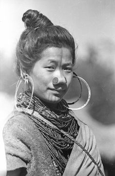 1944 photo of an Apatani woman from North East India, with traditional facial tattoos and nose plugs, beaded necklaces and large hoop earrings.  #TattooHistory #VintageTattoos #VanishingTattoo