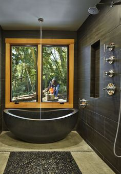 """The Seattle Times: Island cabin offers a place to go outside and play Island cabin offers a place to go outside and play  The master bath features Sara's great find: an oval tub cut from a single piece of black granite (3,700 pounds). She found it online from China. """"I was nervous to do it, but I checked their references and it worked out."""" Outside is a nurse-log view, where Sara fills a bird bath with water."""