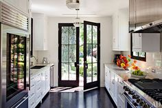 Industrial style french doors complete a monochromatic kitchen in A Glamorous Home in the Hollywood Hills