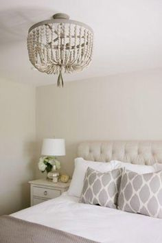 Traditional and timeless neutral bedroom with a wood bead chandelier, tufted ivory linen headboard, patterned throw pillows, classic shaker-style nightstand and table lamp, all rendered in soft shades of ivory and gray.