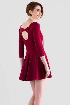 It's easy to go from day to night in the Dellano Bow Back Dress. This deep burgundy a-line dress features a unique texture with a complimentary bow in the back. Style with booties & a satchel for daytime or a statement necklace & heels for a night out!