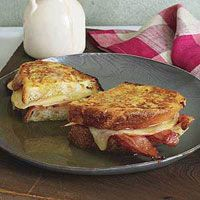 Apple, Cheddar and Bacon Monte Cristos - Hot syrup and crispy bacon pair nicely with melted cheese and apples in this satisfying breakfast sandwich.