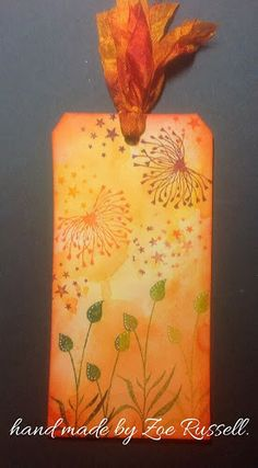 By Zoe Russell. Apply Distress inks to craft mat, spritz with water, and swoosh tag through it. Dry. Stamp.