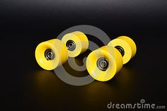 Four yellow rollerskate wheels on a black background