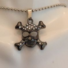 Crystal Skull Pendant Stainless a Steel. About 1 inch long. Comes on a 20 inch chain. Comes with one free hypodermic needle pen.Price is my lowest Jewelry
