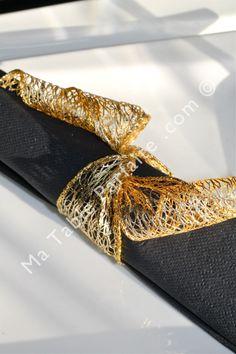 Détail sur la serviette jetable de la décoration de table Paris la nuit. Fabriquée dans une matière aussi douce que la ouate, elle est ici nouée d'un ruban or en laitonné, finement tissé. Nos serviettes sont livrées déjà montées.
