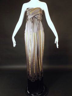 Gorgeous gown in a pewter silk with a gold and black stripe and scrolling along the lower skirt. The dress has an Empire waistline with long sashes that I believe wrap around the bust. The skirt falls