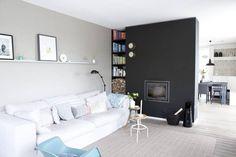 STUE: Minimalistisk stue med peis intergrert i en svart vegg som skiller stue og kjøkken. Baksiden er malt hvit. Resten av interiøret går i lette pastellfarger.