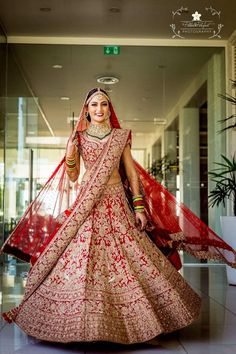 Looking for Bride twirling in red and gold lehenga with green jewellery? Browse of latest bridal photos, lehenga & jewelry designs, decor ideas, etc. on WedMeGood Gallery.
