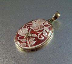 This lovely vintage sterling carnelian pendant features carved rock crystal flowers and a sterling ladybug perched atop the crystal. Not