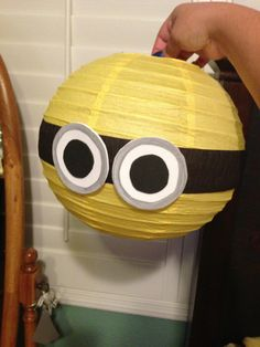 Despicable me minion birthday decorations yellow paper lanterns with black streamers and white and black foam sheets cut in circles and used silver metallic sharpie