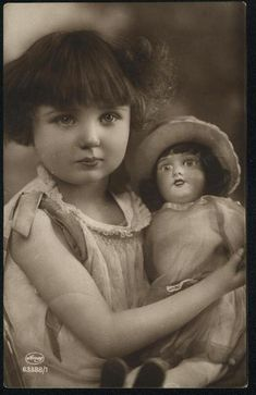 Vintage photo of little girl with doll, circa 1920.