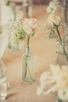 Simple wedding centerpiece in different shapes, sizes bottle and jar, filled in with roses and baby's breath #centerpieces