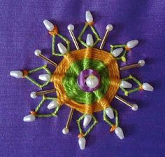 cool whipped wheel with beads - base is lazy daisys with tacking stitches added to the ends
