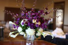 Tall centerpiece of White football mums and calla lilies, purple mini carnations, orchids, and deep purple stock