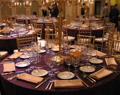 eggplant pintuck tablecloth with champagne linens. Interesting napkin fold and charger display.