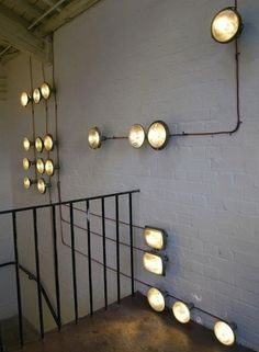 DIY Lighting, Stairway 'Headlights' - Repurposed vintage headlights look perfectly retro chic on a painted brick stairwell. As an added infusion of style, the design created by the fixtures' exposed electrical wiring is reminiscent of abstract geometric art.