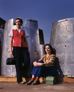 """Nacelle Belles: October 1942. """"Two assembly line workers at the Long Beach, California, plant of Douglas Aircraft Company enjoy a well-earned lunch period. Nacelle parts of a heavy bomber form the background."""" 4x5 Kodachrome transparency by Alfred Palmer for the Office of War Information."""