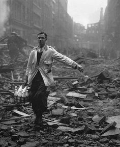 A milkman delivering on a London street devastated during a German bombing raid. 1940.   Fred Morley