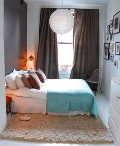 Really cozy #bedroom with very tall curtains. Brick wall painted white, another wall painted dark brown/grayish color.