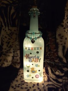 This is a re-purposed wine bottle thats been turned into a beautiful lamp/nite light. The bottle is painted in a lovely blue ocean breeze and features hand beaded jewelry. The words  Sweet Baby are displayed on the front. The back of the bottle has a small hole near the bottom where the lights are fed through. The cord plugs right into the wall. This bottle is sure to add a warm and delightful glow to any room! Perfect for a baby shower gift or any little ones room