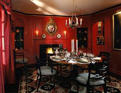 Red and black dining room with a patterned rug and gold accents