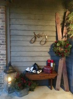 My Christmas porch includes vintage skis, fresh cut cedar and pinecones in a vintage galvanized tub, ice skates and plaid thermos on wooden bench, a lantern, along with rustic metal joy sign