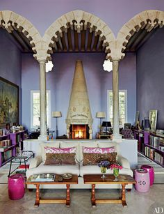 A trio of stone arches creates an enclave at one end of the living room in interior designer May Daouk's late-19th-century Beirut villa; the antique chimneypiece is Italian.
