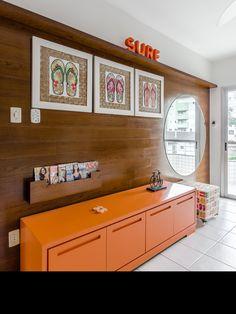 Projeto para um quarto jovem na praia ! Painel em madeira cumaru destaca o movel em laca cor laranja. Este móvel acomoda sapatos, bolsas. O espelho complementa o painel com dois pufes em baixo, que facilita na hora de calçar os sapatos !
