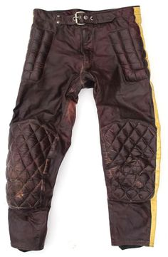 These vintage leather racing pants are brown with yellow racing stripes.  They have padded quilted knees and hips.  The front has a riveted belt. All zippers are Robin brand.  There is a label, but it has worn clean, and is illegible.  Waist: 16″ (doubled = 32″)Inseam: 26″ (meant to be worn with boots)