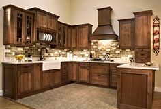 This Kitchen has Rustic Alder Cabinetry with a Coffee glaze finish, with deep drawers, trash and recycle pullout, cooking center, decorative wood hood, Easy Reach Corner cabinet, rollouts, spice pullouts, toekick drawer, deep bin Lazy Susan and more! It Features a Fireclay Farm Sink, Quartz Countertop, and tile splash with metal accents. Phillips Floor To Ceiling - Renovating your kitchen