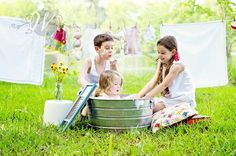 Cutest summer outdoor family photo session idea ever! Laundry as props how fun! Its so adorable how the big brother and sister are giving the baby a bath! Confessions of a Prop Junkie » Photoshoot Inspiration /Siblings / Brothers / Sisters / Child Photography ♥