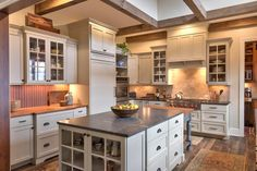 Task lighting sprinkled throughout this expansive kitchen makes prep work a breeze...and friendly to boot! Natural wood accents warm up the crisp white cabinets and fridge.