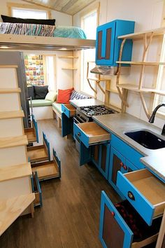 In the kitchen you'll find turquoise blue cabinets, concrete counters, a freestanding gas range, and an apartment size refrigerator. The open shelves have branches as their supports.