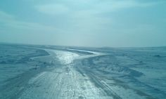 Ice road trucker coming off a portage onto a lake in Northwest Territories Canada.