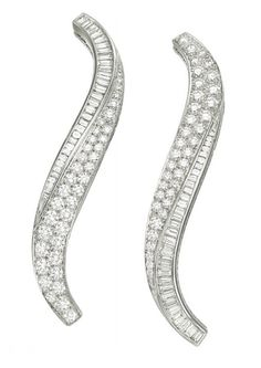 "A PAIR OF DIAMOND ""FLAME"" CLIP BROOCHES, BY VAN CLEEF & ARPELS   Each designed as a tapered scrolling band, with graduated lines of circular and baguette-cut diamonds, mounted in platinum, may also be worn as hair ornaments, with maker's marks, in a Van Cleef & Arpels light green leather case  Signed Van Cleef & Arpels, no. BL 51383"