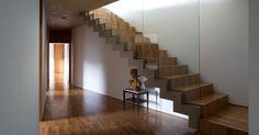 Um lance de escadas revestidas de madeira peroba mica (assim como todo o piso da área íntima) conduz aos dormitórios, no bloco inferior da Casa PL. O guarda-corpo é em vidro laminado e o forro tem acabamento liso em concreto aparente. O projeto é de Fernando Maculan e Pedro Morais